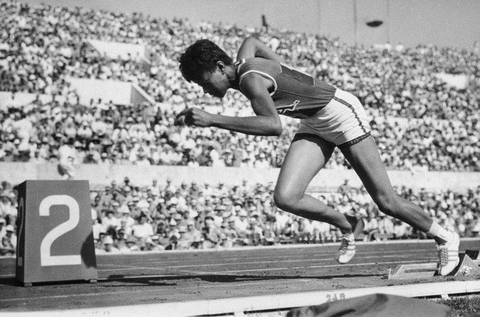 Wilma Rudolph faisant son départ dans une course de sprint, des milliers de spectateurs à l'arrière-plan (© AP Images)