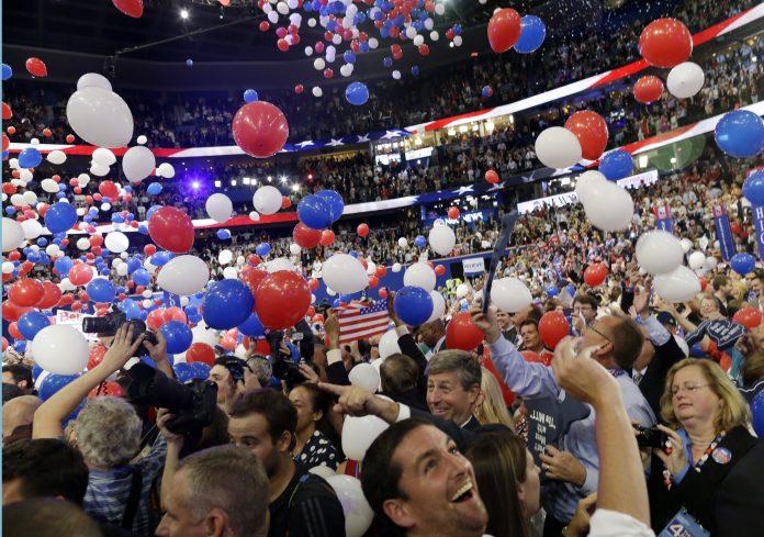 Lâcher de ballons bleus, blancs et rouges dans un amphithéâtre bondé (© AP Images)