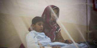 Madre y su hijo en una cama protegida por un mosquitero (© AP Images)