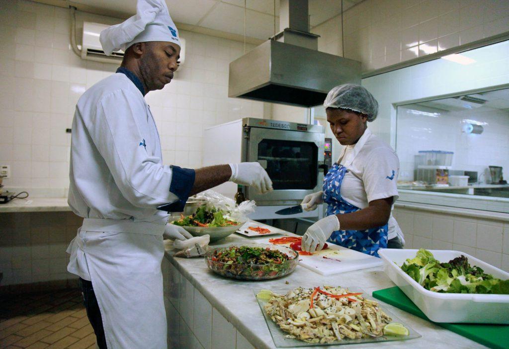 Cocineros preparando alimentos en una cocina (© AP Images)