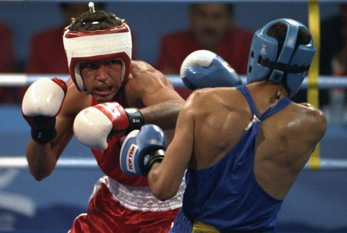 Oscar de la Hoya affrontant un adversaire dans un combat de boxe (© AP Images)
