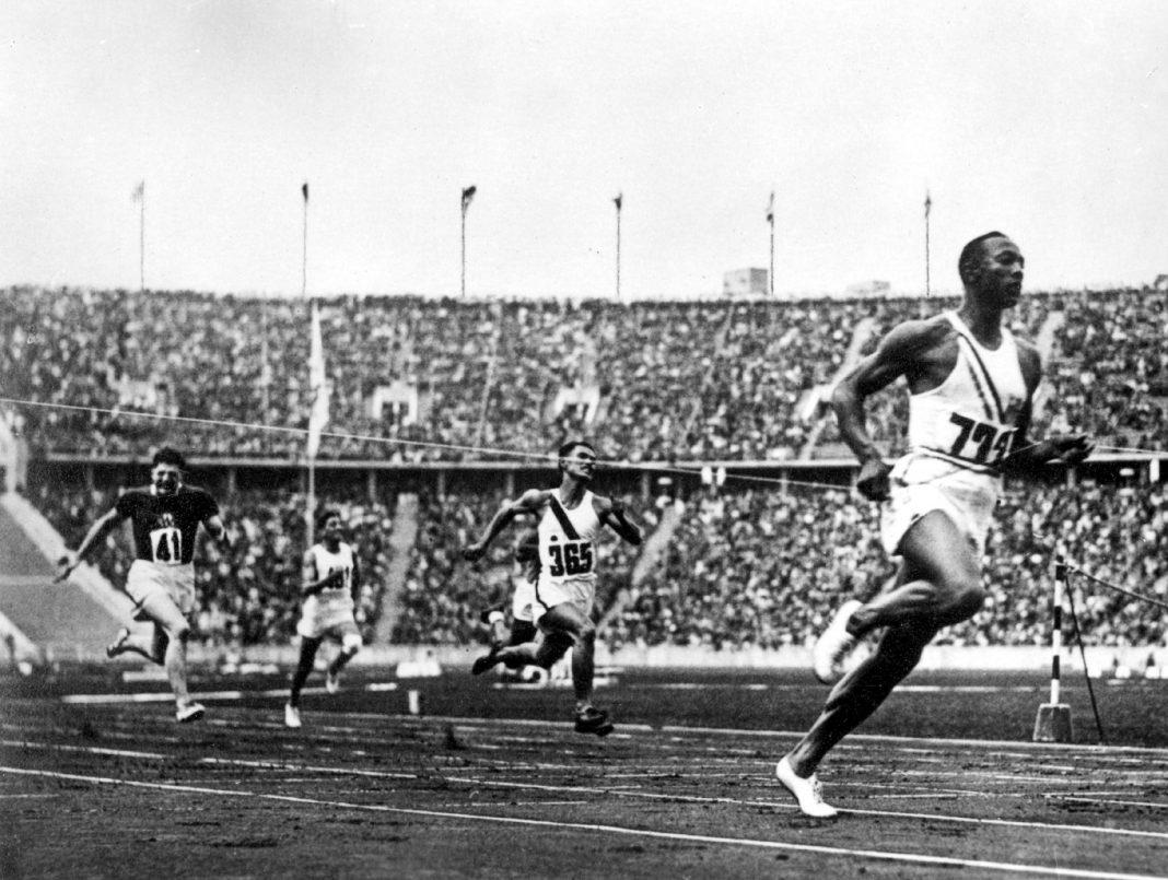 Jesse Owens crossing finish line in race in large stadium (© Alamy/INTERFOTO)