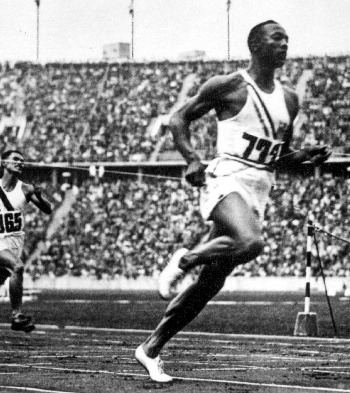 Jesse Owens franchissant la ligne d'arrivée d'une course dans un grand stade (© Alamy/INTERFOTO)