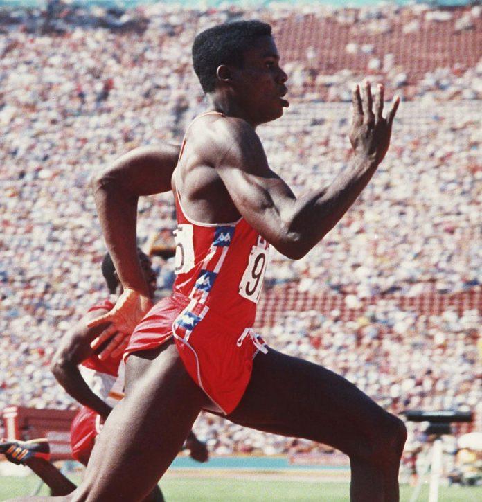 Carl Lewis compete em uma corrida diante de uma grande multidão (© AP Images)