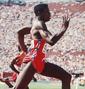 Carl Lewis sprinting in front of large crowd (© AP Images)