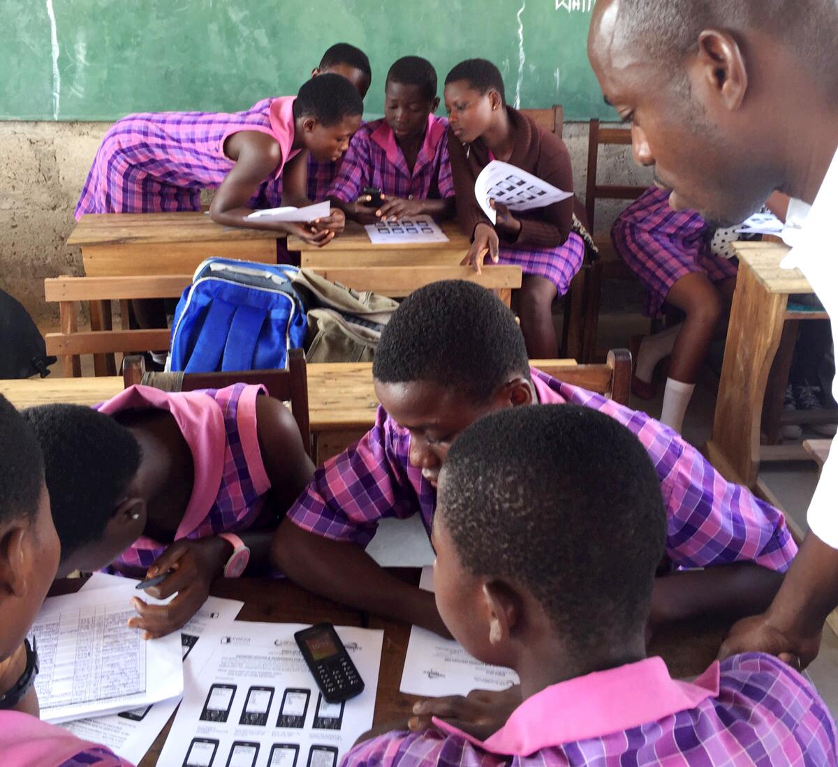 Группы школьников сгрудились за столами, с мобильными телефонами и учебно-методическими материалами (Courtesy of Eneza Education)
