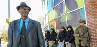 Man wearing hat walking past men in riot gear standing outside a building (Getty Images/Lloyd Fox/Baltimore Sun)