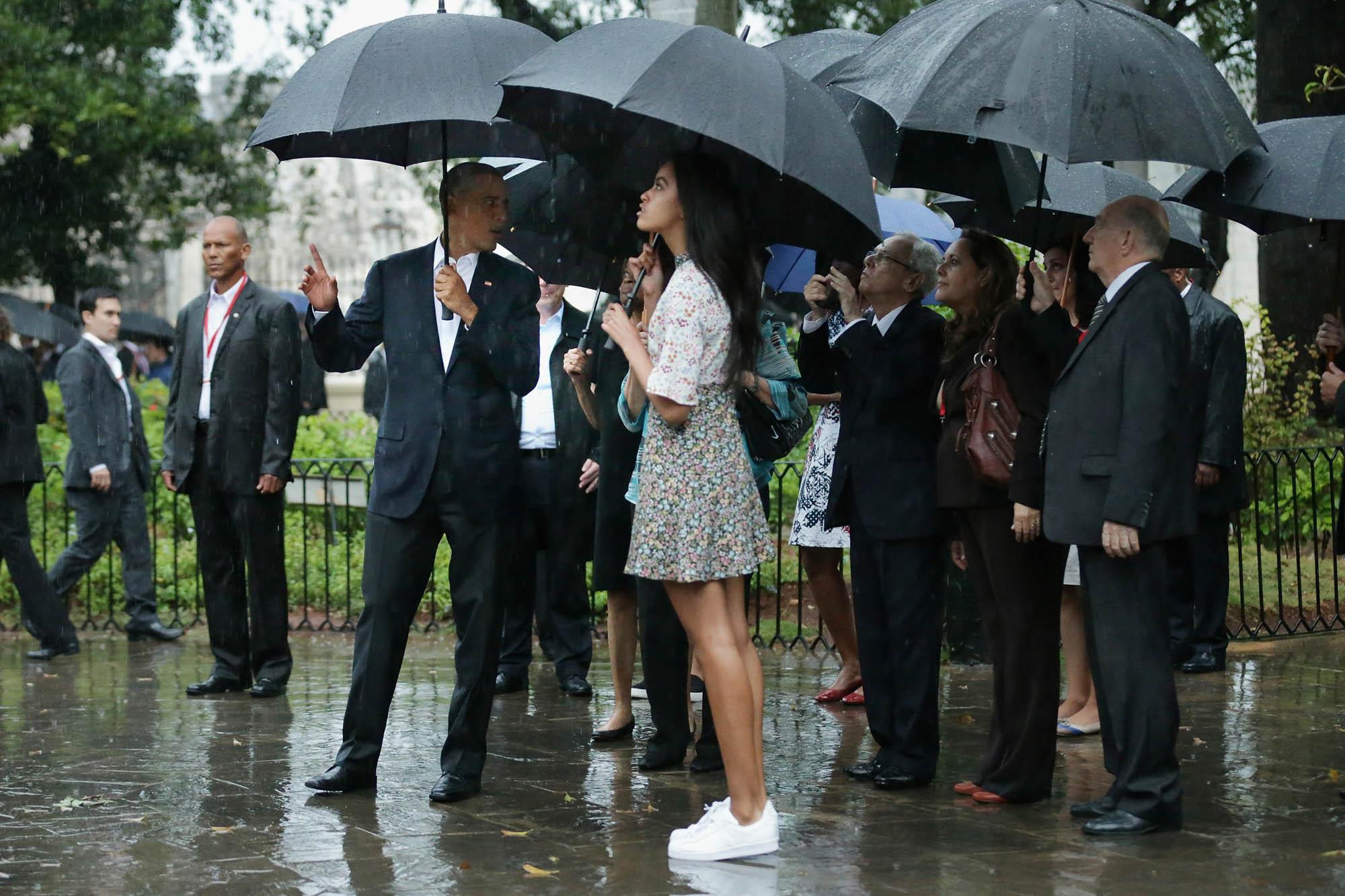 O presidente Obama, Malia Obama e outras pessoas na chuva com guarda-chuvas (Imagens Getty/ Chip Somodevilla)