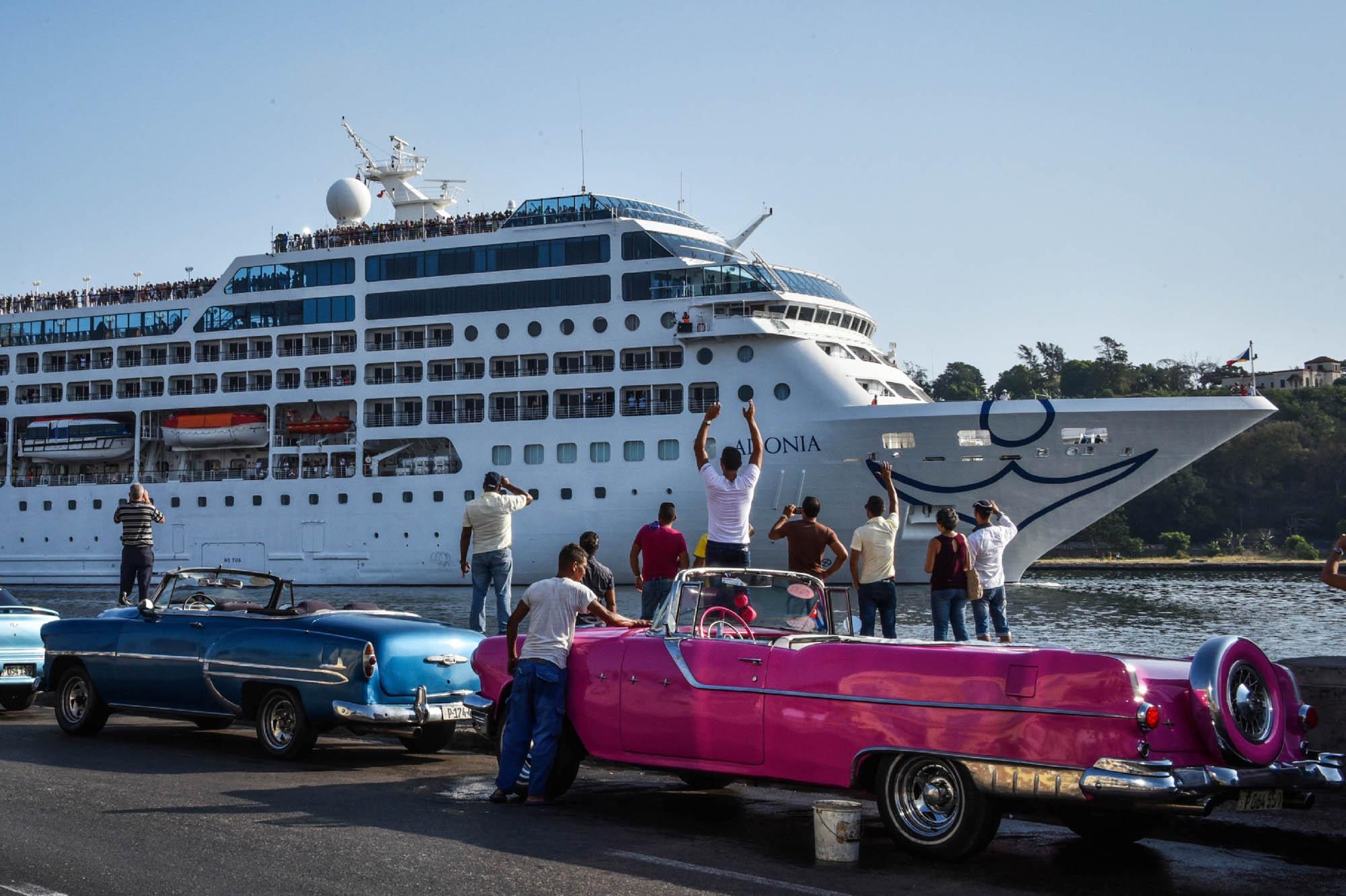 Pessoas em cima de um carro rosa acenando para um navio de cruzeiro (AFP/Getty/Adalberto Roque)