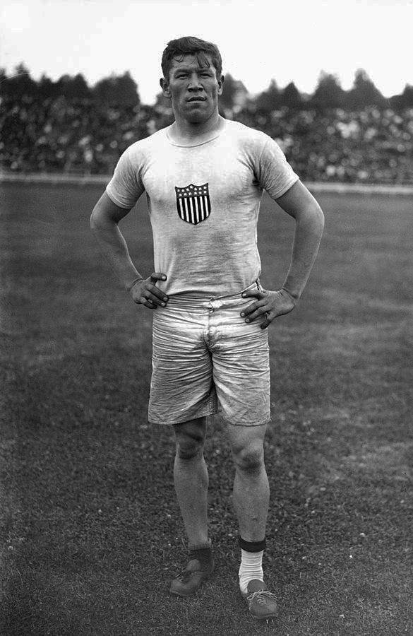 Jim Thorpe de pé com as mãos nos quadris (Domínio público)