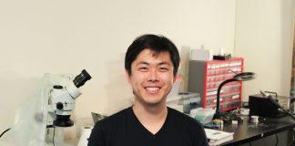 Raymond Wu, souriant, assis devant une table où est posé un microscope (Crédit photo : Wynd)