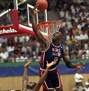 Michael Jordan jumping and knocking basketball away from hoop (© AP Images)