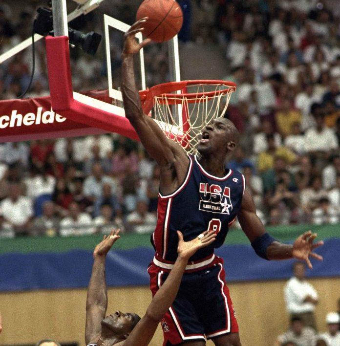 Michael Jordan salta e rebate bola de basquete para longe do aro (© AP Images)