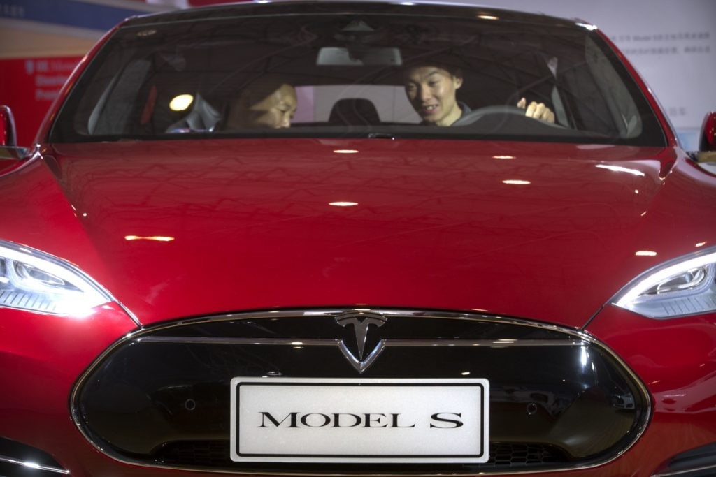 Two people sitting inside an electric car (© AP Images)