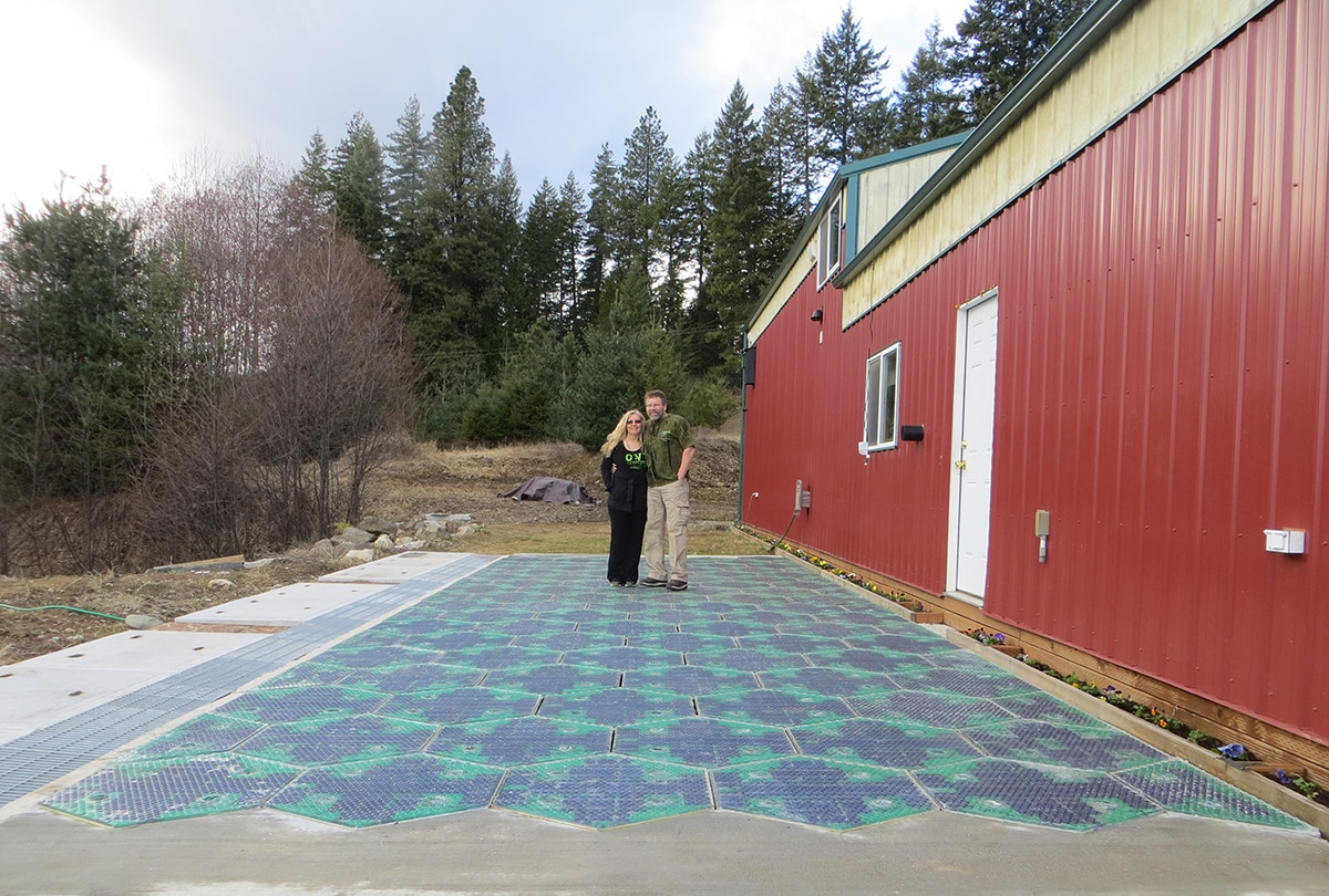 Couple standing on hexagonal roadway panels next to red building (Courtesy of Solar Roadways)