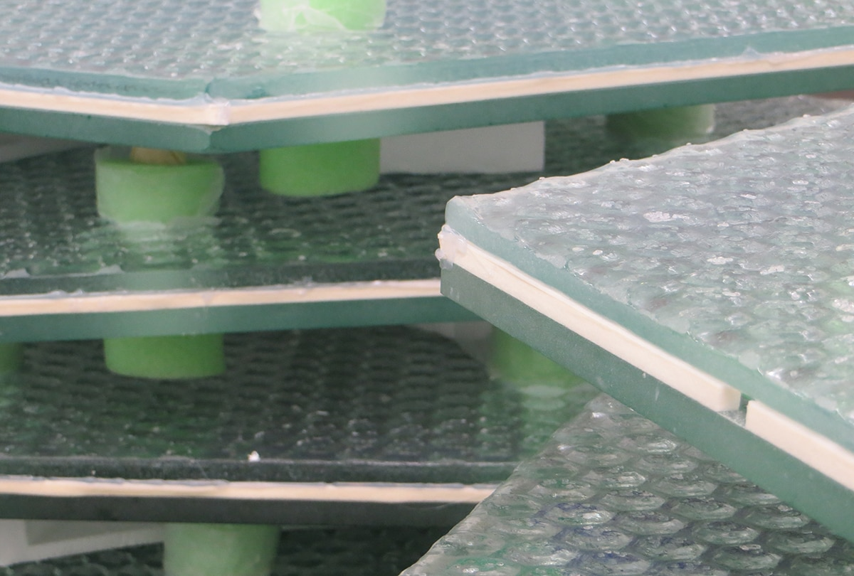 Stacks of thick glass panels inset with hexagonal glass pieces (Courtesy of Solar Roadways)