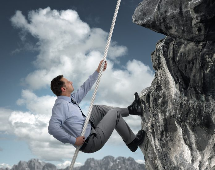 Man in business attire using rope to climb mountain (© Shutterstock/Brian A. Jackson)