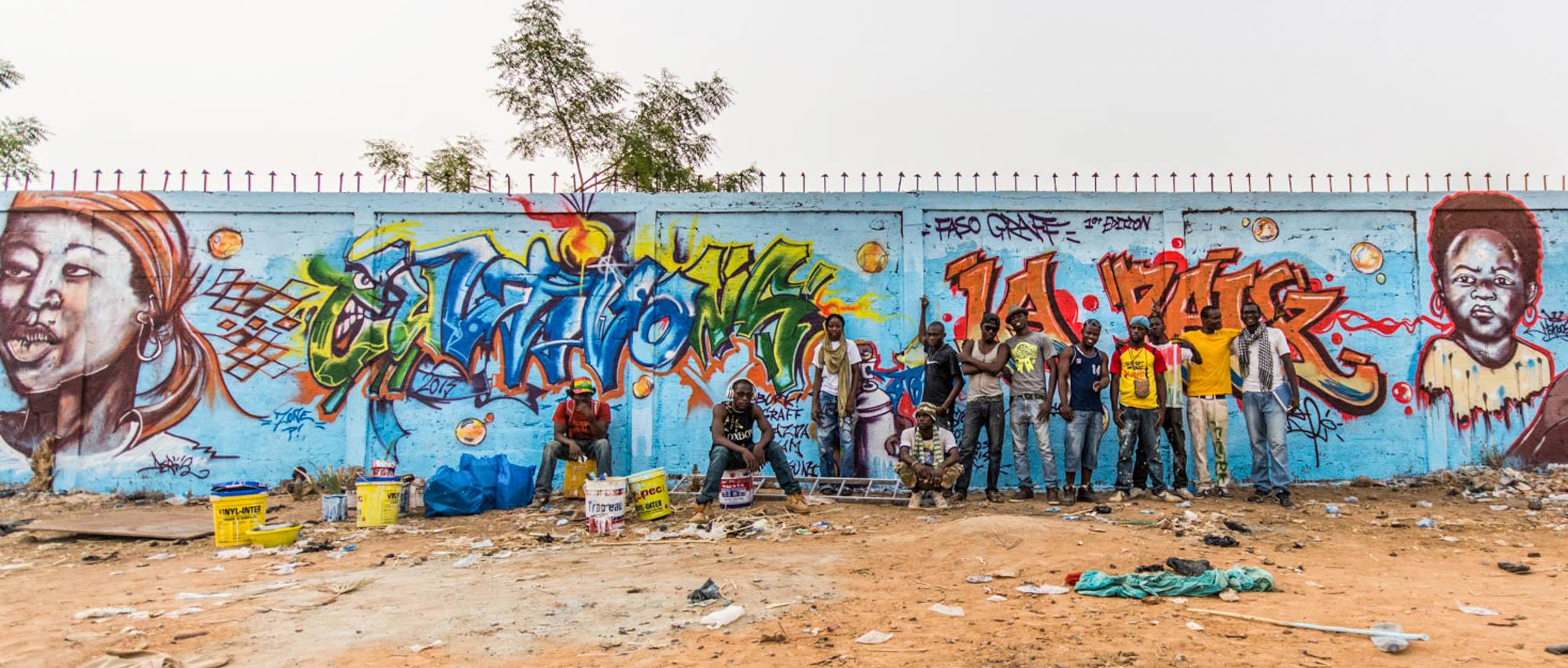 Artistas posando ante un mural de grafiti. (© Erwan Rogard)
