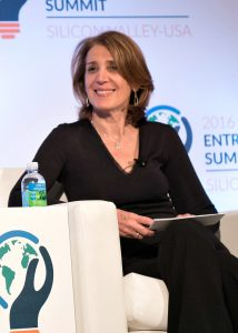 Ruth Porat sitting in chair on stage, smiling (Ben Solomon/State Dept.)