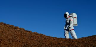 Person in space suit walking outdoors (University of Hawai'i)