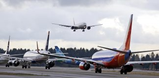 Planes lining up to take off as a jet is landing (© AP Images)