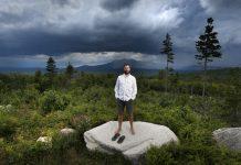Man standing on boulder in wilderness (© AP Images)