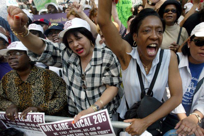 Des manifestants brandissant des pancartes et levant le bras, poing fermé (© AP Images)