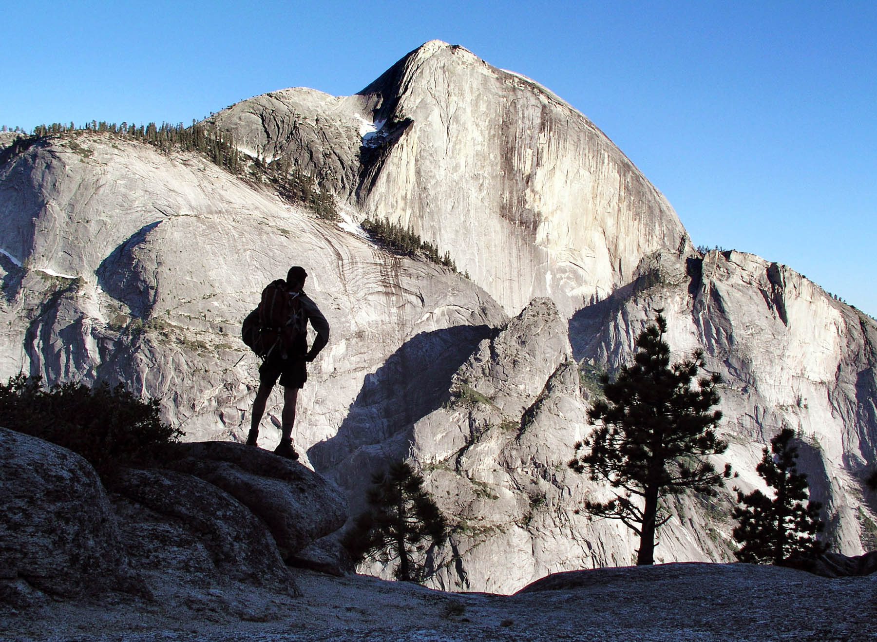 Silueta de un hombre parado sobre unas rocas mirando una pared rocosa (© AP Images)