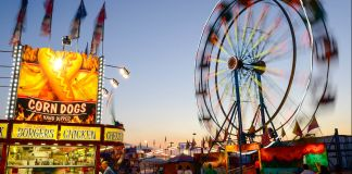 Corn dog stand and Ferris wheel at sunset (© AP Images)