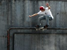 Skateboarder grinding on pipe attached to concrete wall (© AP Images)