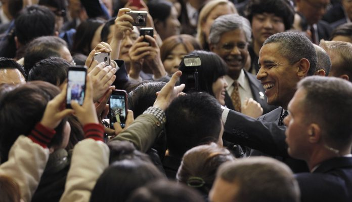Smiling President Obama surrounded by people taking pictures (© AP Images)