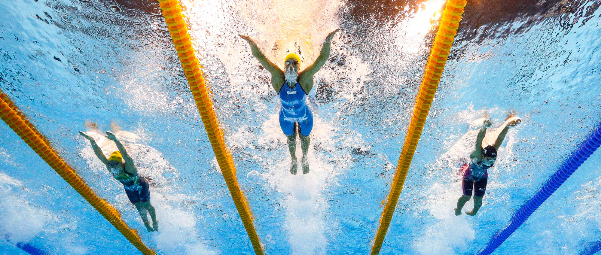 Three women swimming viewed from underwater (© AP Images)