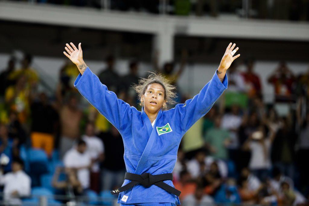 Olympian judo winner raising her hands (© AP Images)