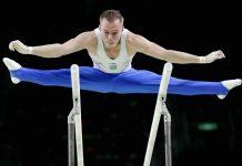 Oleg Verniaiev in the air, straddling the parallel bars (© AP Images)