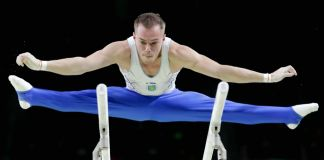 Oleg Verniaiev in the air, straddling the parallel bars (© AP Images)