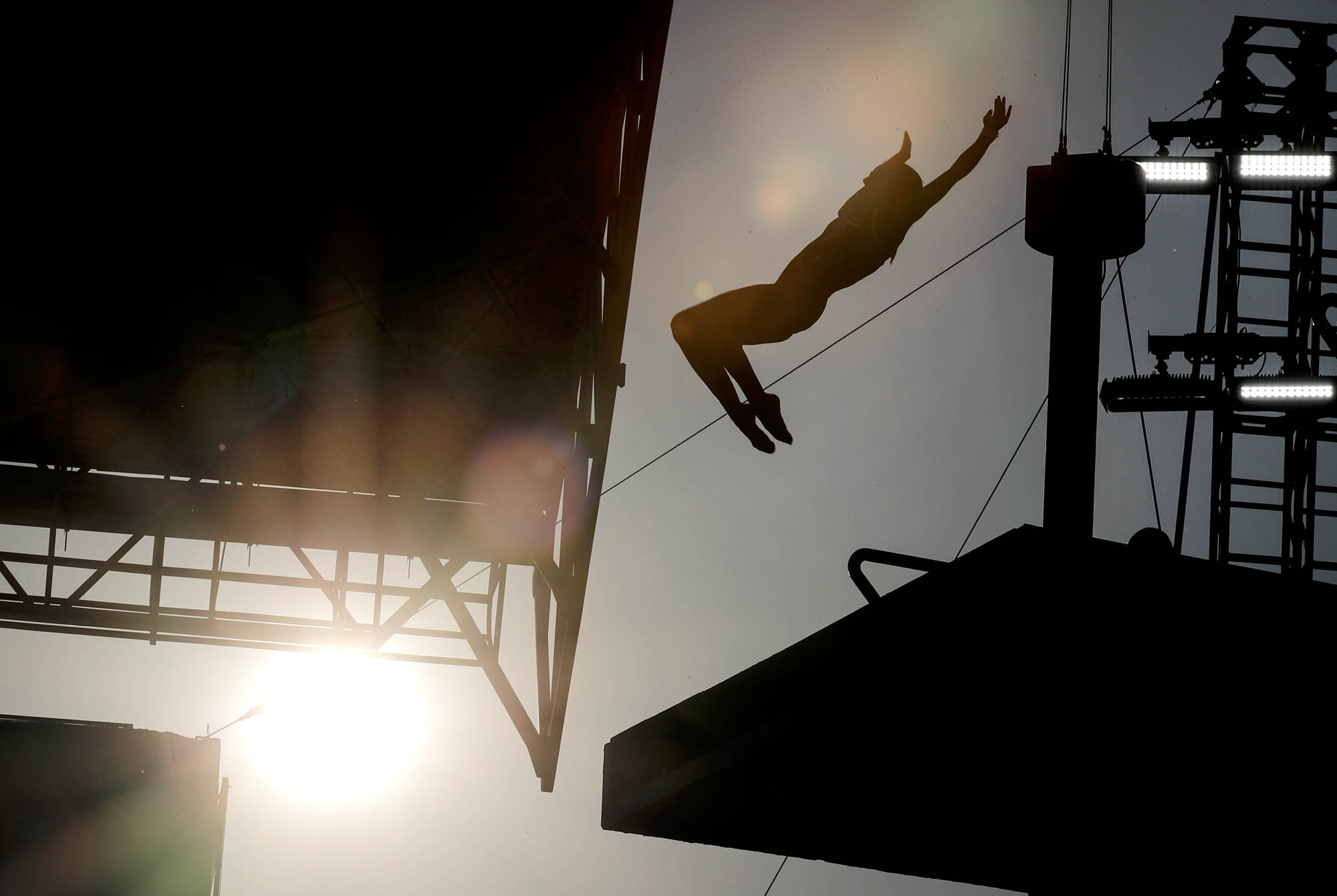 Silhouette of person diving off platform (© AP Images)