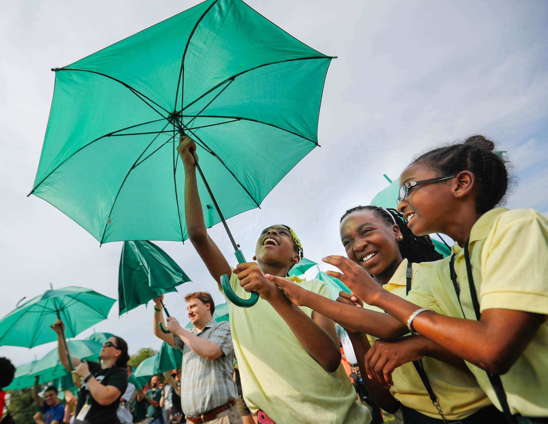 Young girls and other people holding green umbrellas (© AP Images)