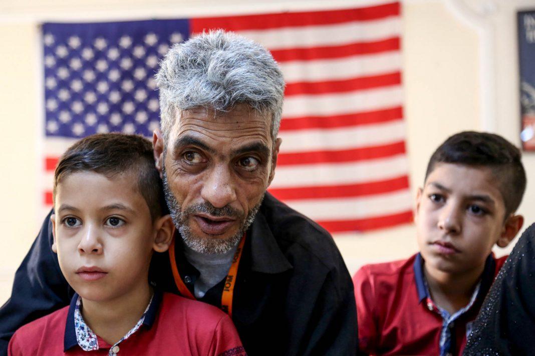 Deux jeunes garçons avec leur père, regardant au loin, un drapeau américain en arrière-plan (© AP Images)