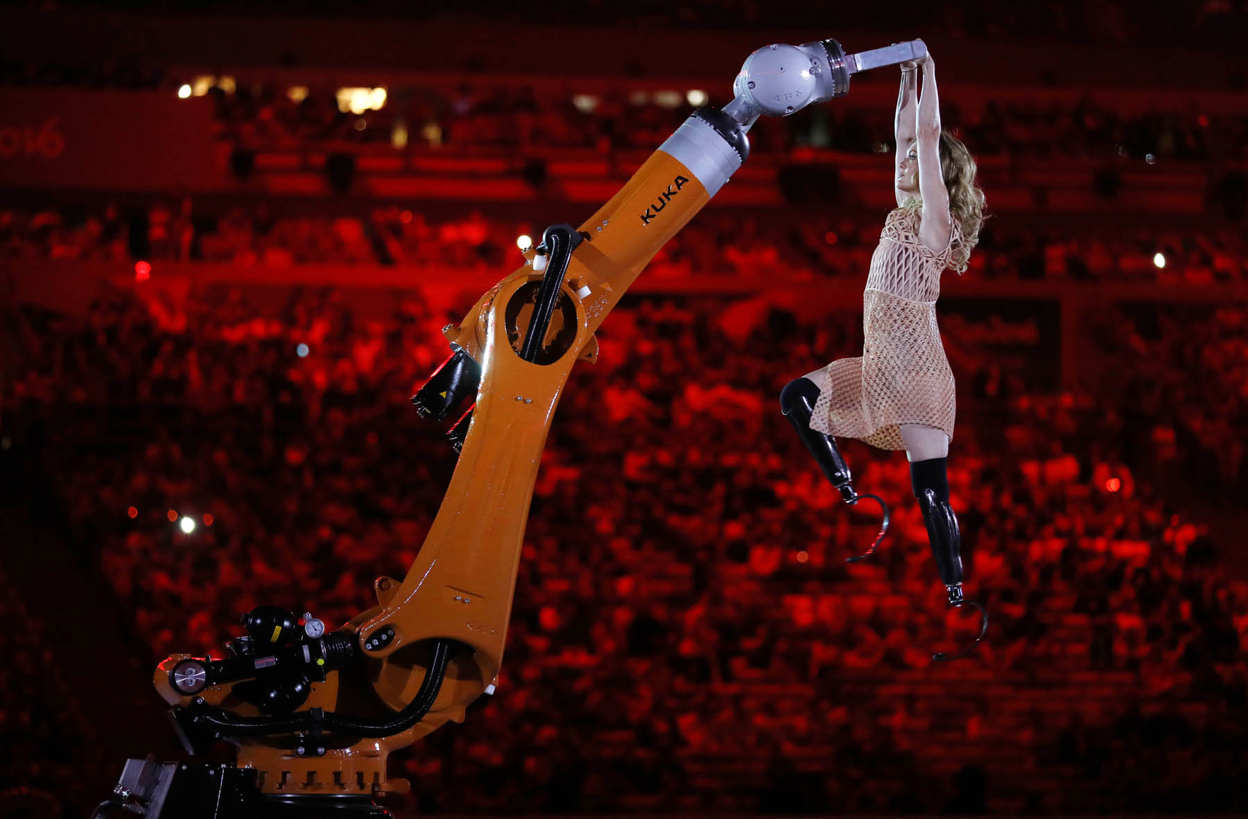 Robot arm lifting amputee Amy Purdy in stadium (© AP Images)