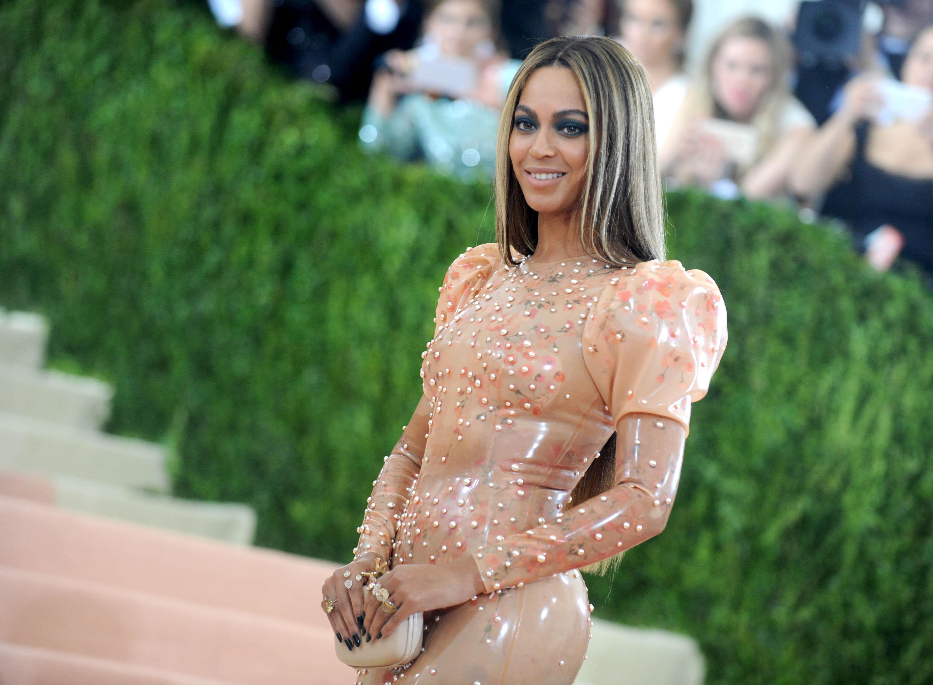Beyoncé en un brillante traje de fiesta de látex de color melocotón (© AP Images)