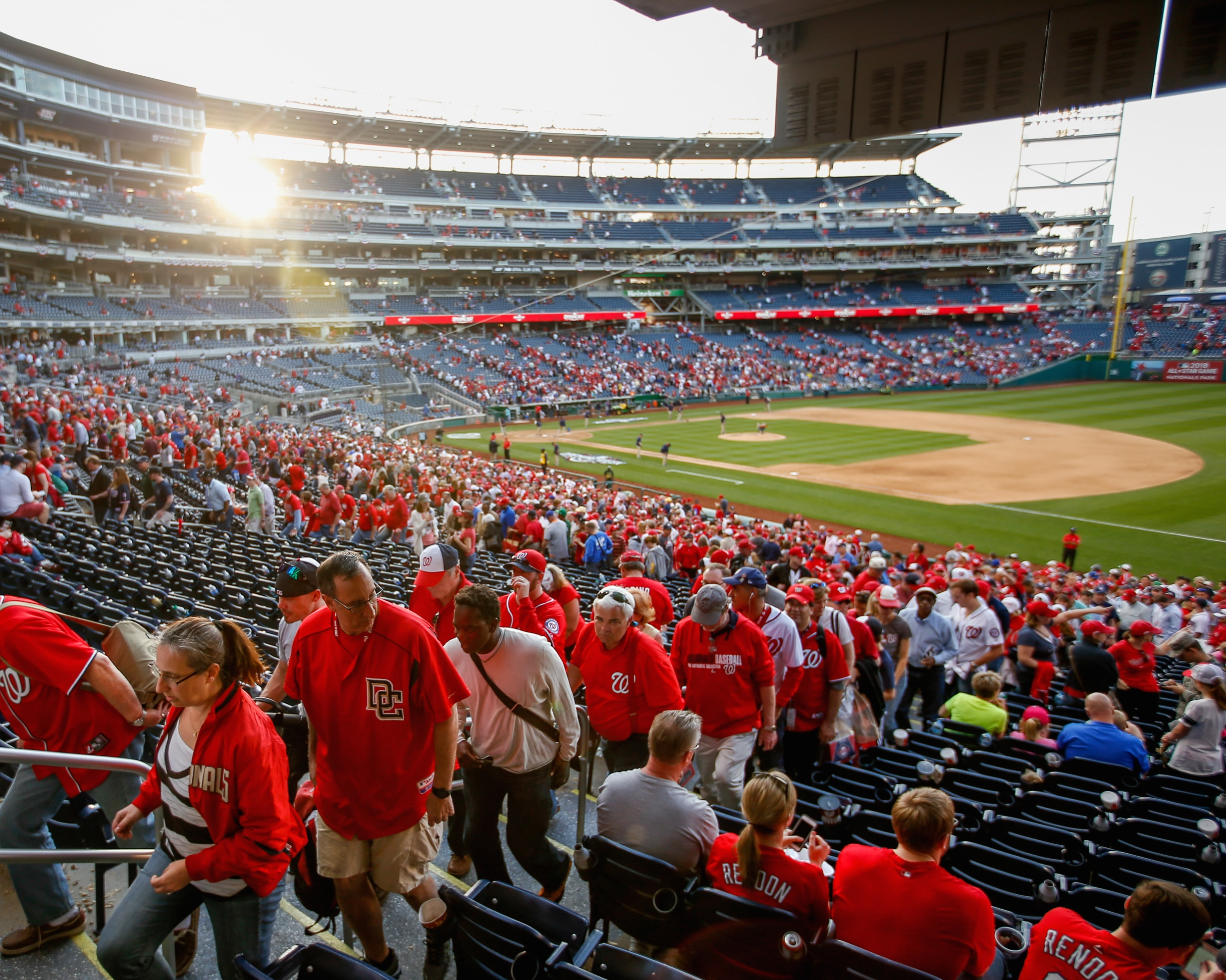 Baseball fans dressed in Nationals apparel leaving stadium (© AP Images)