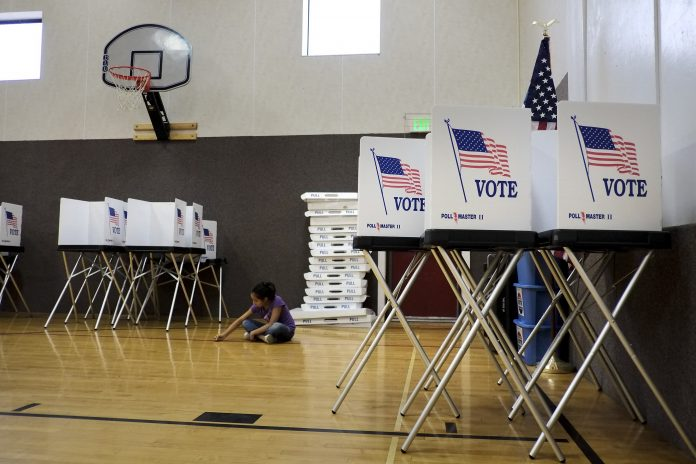 Voting booths set up in gymnasium (© AP Images)