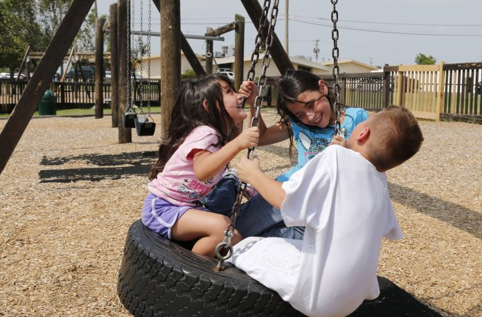 Children on a tire swing (© AP Images)