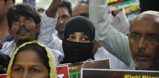 Indians holding signs in protest (© AP Images)