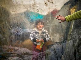 Criança em pé com a mão estendida atrás de uma tenda coberta por um plástico (© AP Images)
