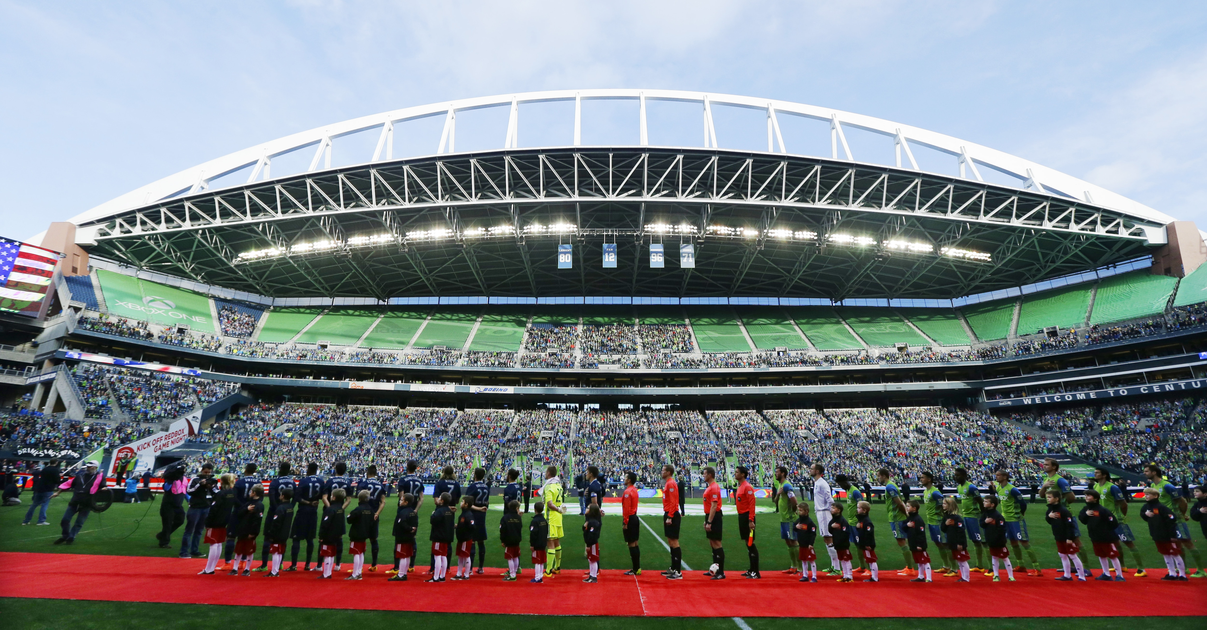 Teams lining up on red carpet over football field with seated crowd in stadium (© AP Images)