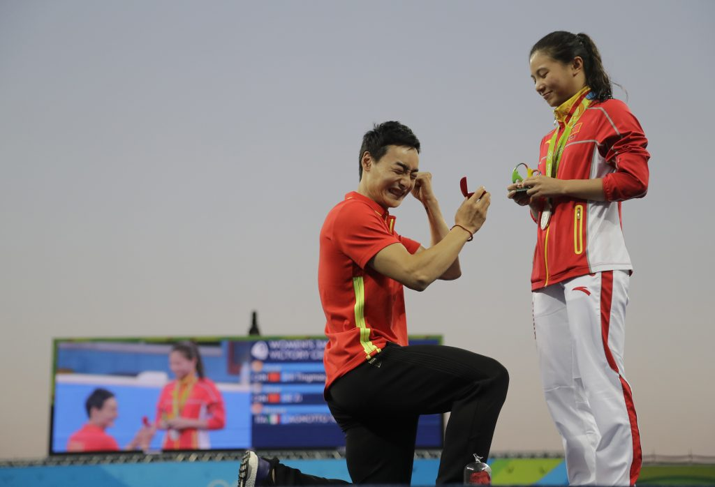 Man kneeling, proposing marriage to woman near Olympic pool (© AP Images)