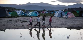 Children standing near tents and puddle of water (© AP Images)