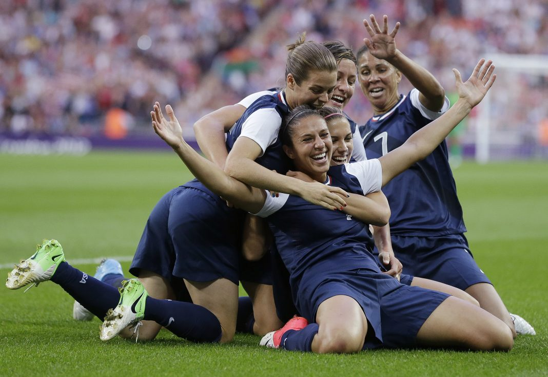 Carli Lloyd kneeling on field, celebrating goal with teammates (© AP Images)