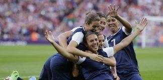 Carli Lloyd, de rodillas en el campo, celebrando su gol con sus compañeras de equipo (© AP Images)
